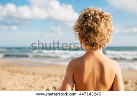 Back view of shirtless boy with curly hair against of beautiful seascape