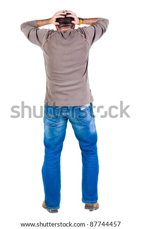 Back view of shocked and scared young  man. Holds hands upwards. Rear view. Isolated over white background. - stock photo