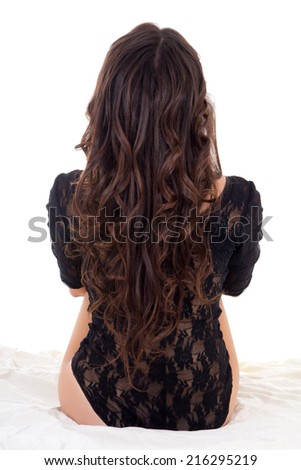 back view of sitting woman in black lingerie isolated on white background
