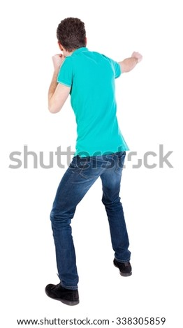 back view of skinny guy funny fights waving his arms and legs. Isolated over white background. Rear view people collection.  backside view of person. The guy in the blue sweater fights