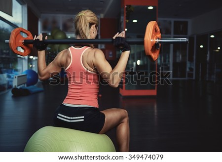 Back view of slim athletic woman with muscular body holding barbell exercising in gym. Concept of strength, health and endurance.   - stock photo