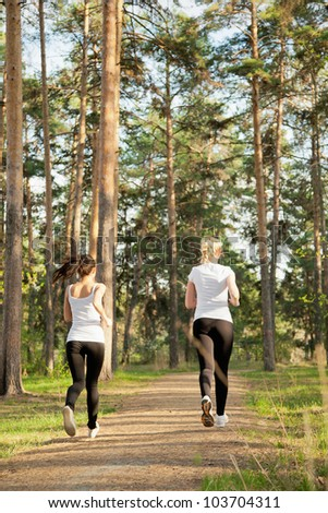 Back view of slim runners jogging in the park - stock photo