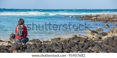 Back view of sports young woman with backpack sits on the beach and looks at the sea - stock photo