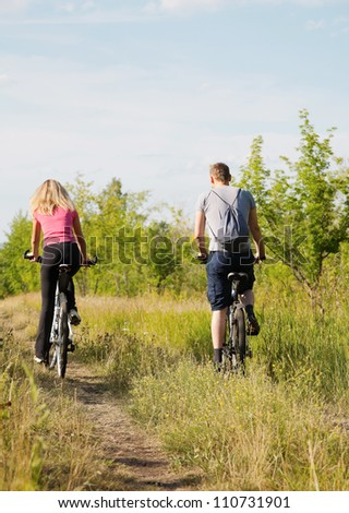 Back view of sporty couple riding bicycles  in the forest - stock photo