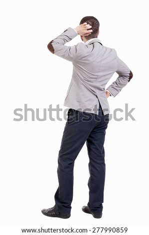 back view of standing business man. Young businessman scratches his head in amazement. Rear view people collection.  backside view of person.  Isolated over white background.  - stock photo