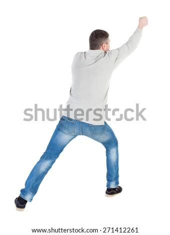 back view of standing man pulling a rope from the top or cling to something. guy watching. Rear view people collection.  backside view of person.  Isolated over white background. - stock photo