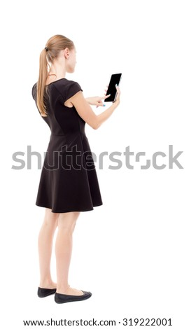 back view of standing young beautiful  girl with tablet computer in the hands of. girl  watching. Rear view people collection.  backside view of person.  Isolated over white background.  - stock photo