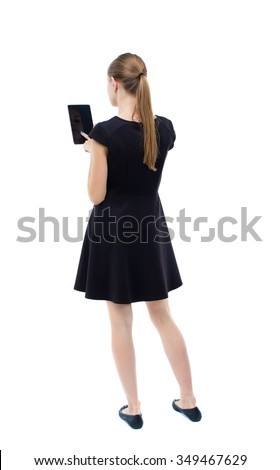 back view of standing young beautiful  girl with tablet computer in the hands of. girl  watching. Isolated over white background. blonde in a black dress presses a finger on screen of your smartphone - stock photo
