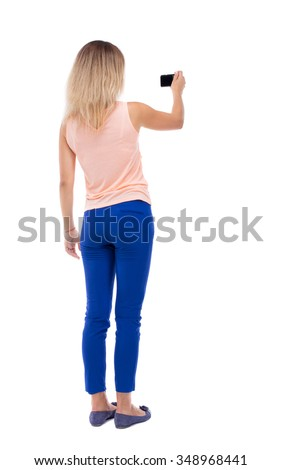 back view of standing young beautiful  woman  and using a mobile phone. girl  watching.   Isolated over white background. Blonde in blue pants makes video holding the camera with one hand. - stock photo