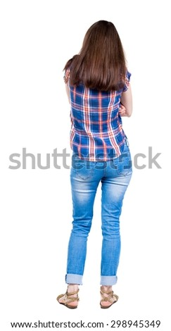 back view of standing young beautiful  woman.  girl  watching. Rear view people collection.  backside view of person.  A young girl in a checkered blue with red stripes is folded arms from the cold. - stock photo