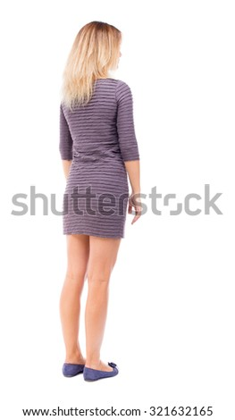 back view of standing young beautiful  woman.  girl  watching. Rear view people collection.  backside view of person.  Isolated over white background. A girl in a purple dress stands sideways - stock photo