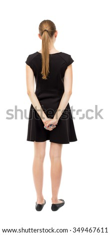 back view of standing young beautiful  woman.  girl  watching. Rear view people collection.  backside view of person.  The blonde in a black dress standing with hands clasped behind his back. - stock photo