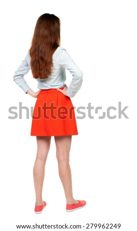 back view of standing young beautiful  woman in dress.  Rear view people collection.  backside view of person.  Isolated over white background. A woman in a red skirt standing with hands on hips. - stock photo