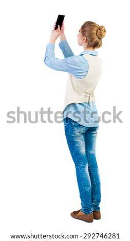 back view of standing young beautiful  woman  in vest and using a mobile phone. girl  watching.    Isolated over white background. Girl in sleeveless photographs on something at the top of the phone.