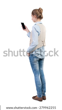 back view of standing young beautiful  woman  in vest and using a mobile phone. Rear view people collection.  backside view of person.  Isolated over white background. Bored girl staring at the phone. - stock photo