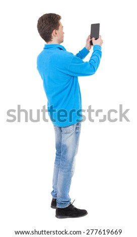back view of standing young man with tablet computer in the hands of. Rear view people collection.  backside view of person.  Isolated over white background. guy in the blue sweater pictures of tablet - stock photo