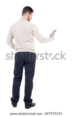 back view of standing young man with tablet computer in the hands of. Rear view people collection.  backside view person. Isolated over white background. bearded man in black trousers looks at plate. - stock photo