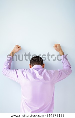 Back view of stressed business man with hands up against the wall - stock photo