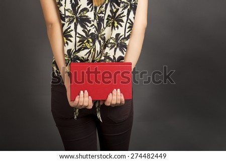 Back view of student woman holding a red  book over gray background - stock photo