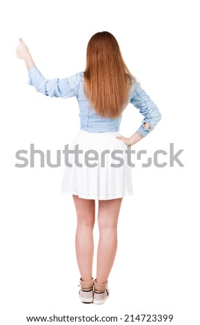 Back view of successful woman thumbs up. Rear view people collection. backside view of person. Isolated over white background. slender redhead in a dress shows hitchhiking - stock photo