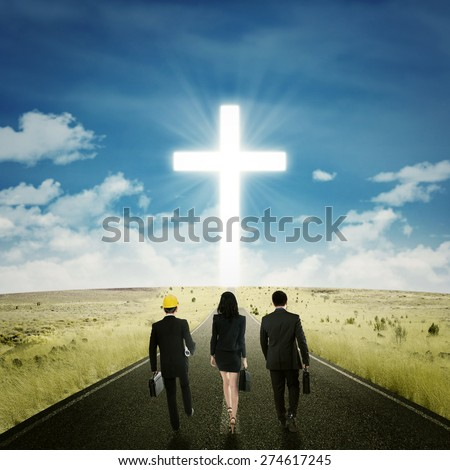 Back view of three businesspeople walking on the road toward a cross - stock photo