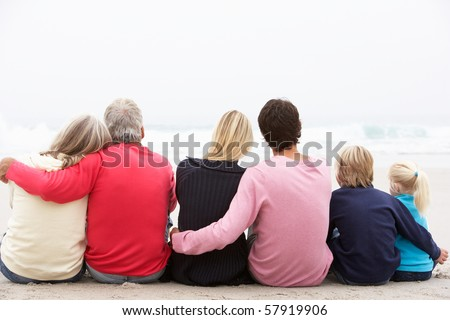 Back View Of Three Generation Family Sitting On Winter Beach Together - stock photo