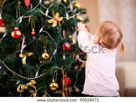 Back view of toddler girl decorating Christmas tree - stock photo