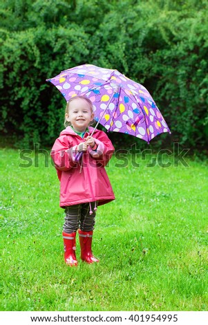 Back view of toddler girl with umbrella outdoors at rainy day