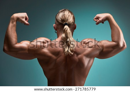 back view of torso of attractive male body builder on blue background. - stock photo