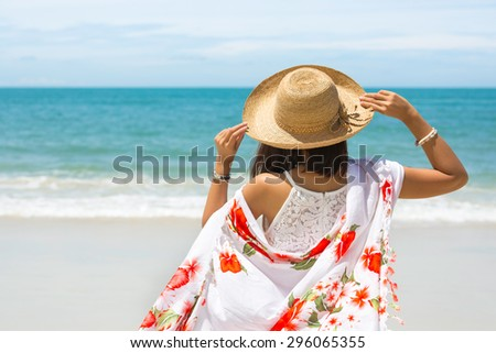 Back view of Travel asia woman with hat and dress looking out of sea on a beach in summer, Koh Samet, Thailand - stock photo
