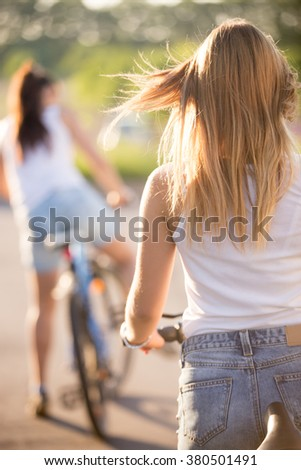 Back view of two beautiful teenage girls starting bikes ride wearing casual white tank tops and jeans shorts on park road on bright sunny summer day - stock photo