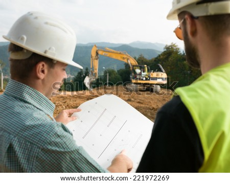 back view of two contractors looking at construction plan on worksite - stock photo