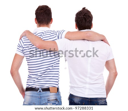 back view of two friends  standing embraced and looking at something on white background - stock photo