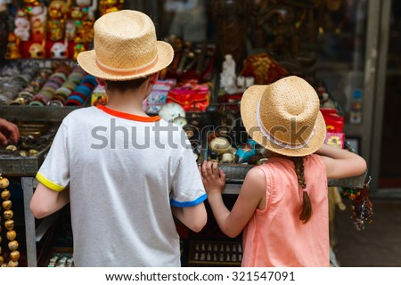 Back view of two kids brother and sister at flea market - stock photo