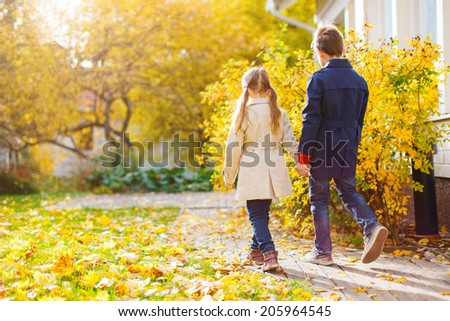 Back view of two kids walking in a beautiful park at sunny autumn day - stock photo