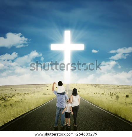 Back view of two parents standing on the road with their children looking at a cross - stock photo