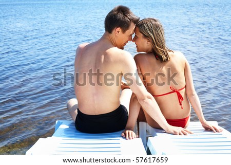 Back view of two people sitting on deck chairs and looking at one another on resort - stock photo