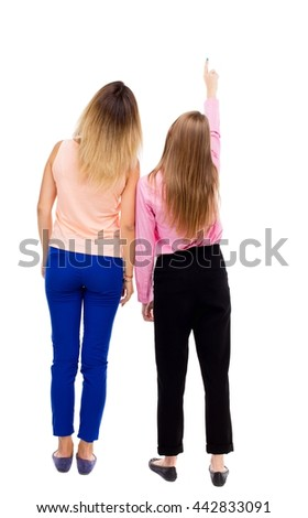 Back view of two pointing young girl. Rear view people collection.  backside view of person. Isolated over white background. The two girls looked up staring at something in the sky. - stock photo