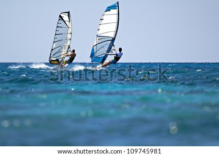 Back view of two windsurfers in action mooving parallel to each other - stock photo