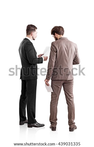 Back view of two young businessmen in suits discussing contract. Isolated on white background