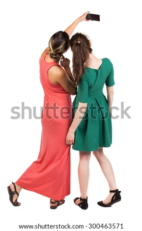 Back view of two young woman photographed on a mobile phone. Rear view people collection. Rear view. Isolated over white background. Two girlfriends are photographing themselves on the phone. - stock photo
