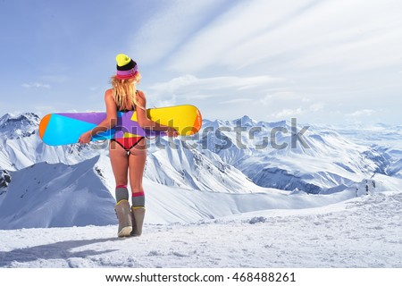 Back view of unrecognizable blonde girl in bikini swimsuit with snowboard in outstretched arms above head against of snowy mountains in sunlight