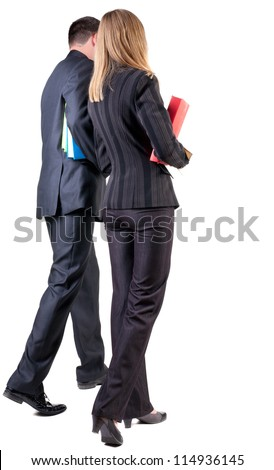 Back view of walking business team. Going young couple with books. beautiful friendly girl and guy in suit . Rear view people collection. backside view of person. Isolated over white background - stock photo