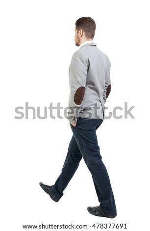 Back view of walking businessman. bearded man in a gray jacket goes on a diagonal with his hands in his pockets.