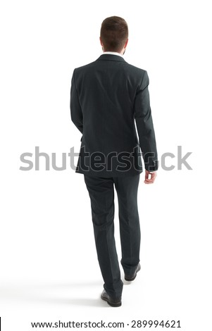back view of walking businessman in black suit. isolated on white background - stock photo