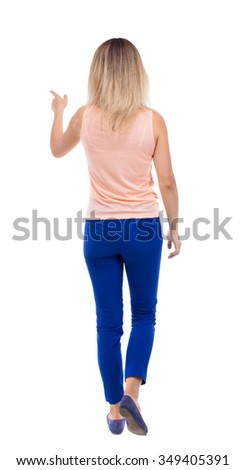 back view of walking  woman. beautiful girl pointing.  backside view of person.  Rear view people collection. Isolated over white background. The blonde in a pink jacket goes forward pointing to left. - stock photo