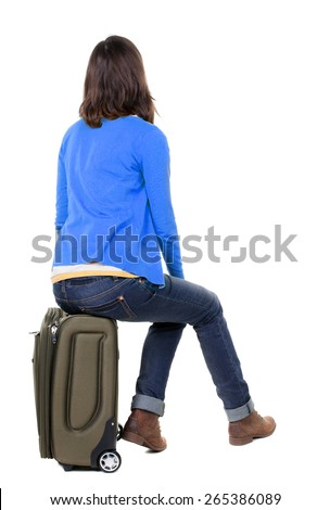 back view of walking  woman  in cardigan sits on a suitcase. beautiful  girl in motion.  backside view of person.  Rear view people collection. Isolated over white background. - stock photo