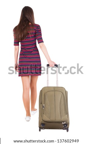 back view of walking  woman  with green suitcase. beautiful brunette girl in motion.  backside view of person.  Rear view people collection. Igirl in a striped dress goes ahead with travel bag - stock photo