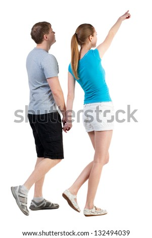 Back view of walking young couple (man and woman) pointing. curious wife shows her husband attractions. Rear view people collection. backside view of person. Isolated over white background - stock photo