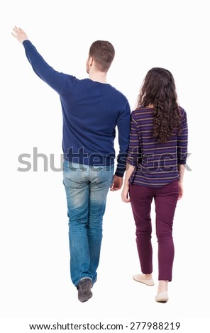 Back view of walking young couple (man and woman) pointing. Rear view people collection. backside view of person. Isolated over white background. Bearded man and curly girl go and look to the side. - stock photo